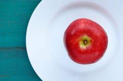 Vlak leg mening van een verse rode appel die op een witte plaat wordt gediend Stock Fotografie