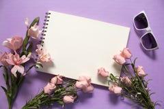 Vlak leg met rozen en zonnebril op violette achtergrond Romantisch roze bloemboeket Royalty-vrije Stock Afbeeldingen