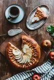 vlak leg met stuk van eigengemaakte appeltaart, cakeserver, kop van koffie en verse appelen stock afbeelding