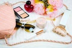 Vlak leg met vrouwelijk zak, schoonheidsmiddelen, zonnebril, parfume en gezichtspoeder Manierconcept op witte achtergrond stock fotografie