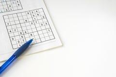 Vlak leg onopgeloste sudoku, blauwe pen, op witte lijst Ruimte voor tekst stock afbeelding