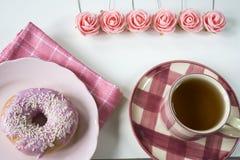 Vlak leg roze ontbijt met rozen, kop thee, servet en doughnut op plaat stock foto
