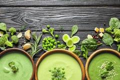 Vlak leg samenstelling met de verschillende soepen van verse die groentedetox van groene erwten, broccoli en spinazie in schotels royalty-vrije stock afbeelding