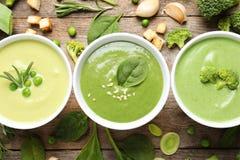 Vlak leg samenstelling met de verschillende soepen van verse die groentedetox van groene erwten, broccoli en spinazie in schotels stock foto's