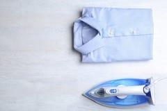 Vlak leg samenstelling met gevouwen schoon overhemd en modern ijzer op lichte lijst royalty-vrije stock fotografie