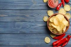 Vlak leg samenstelling met heerlijke knapperige chips op houten lijst stock foto