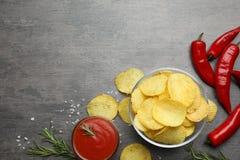 Vlak leg samenstelling met heerlijke knapperige chips op lijst stock foto's