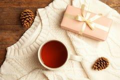 Vlak leg samenstelling met kop van hete de winterdrank en verwarm gebreide sweater op houten achtergrond royalty-vrije stock afbeelding