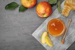 Vlak leg samenstelling met kruik van honing, appelen en dipper stock afbeeldingen