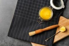 Vlak leg samenstelling met verduidelijkte boter en het bedruipen borstel op grijze achtergrond stock foto's