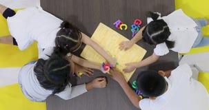 Vlak leg scènevideo van Aziatische studenten die kleurrijk Alfabetstuk speelgoed spelen door in zijn blok samen te brengen stock videobeelden