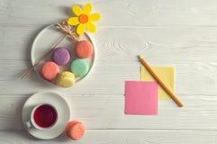 Vlak leg Sluit omhoog Heldere kleurrijke Franse macarons, gele gevoelde bloem, een kop van bessenthee, een potlood, stickers De r royalty-vrije stock afbeelding