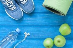 Vlak leg sportschoenen, fles water, mat en oortelefoons op blauw stock foto