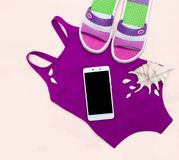 Vlak leg strandtoebehoren: zwempak, sandals, telefoon, zeeschelpen stock afbeelding