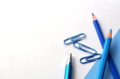 Vlak leg van blauwe potloden, boek en paperclippen met exemplaarruimte Stock Afbeeldingen
