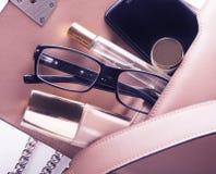 Vlak leg van de roze zak van de leervrouw uit open met schoonheidsmiddelen en toebehoren op witte achtergrond Royalty-vrije Stock Afbeelding