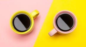 Vlak leg van een twee koffiekoppen met roze en geel stock foto