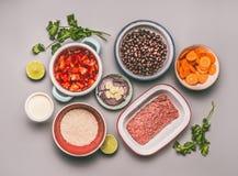 Vlak leg van kommen met het koken van ingrediënten voor evenwichtig één panmaaltijd met bonen, gehakt, rijst stock fotografie