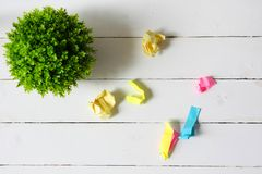 Vlak leg van kunstmatige groene installatie en verfrommel kleurrijke documenten stock foto