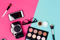 Vlak leg van make-upproducten, smartphone, glazen en filmcamera op kleurrijke achtergrond stock fotografie