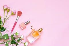 Vlak leg van vrouwelijke schoonheidsmiddelenproducten en toebehoren Een fles van parfum, naakt nagellak, parelearings en rozen ov Royalty-vrije Stock Foto