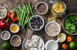 Vlak leg vegetarisch gezond geplaatst voedsel - korrels, groenten, fruit, deegwaren, zaden op een bruine houten achtergrond, hoog stock fotografie