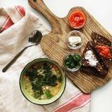 Vlak leg voedselstilleven van lichte snacks van brood, tomaat, worsten en kop van soep Royalty-vrije Stock Foto's