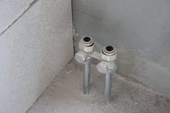 Vlakke buizenstelselwarmtewisselaar twee pijpen puilen van de vloer uit tijdens reparaties aan de muur de vervanging van de batte stock foto's