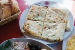 Vlakke die cake met kruiden in vier stukken, stuk worden verdeeld plaat van groenten en stukken van brood Royalty-vrije Stock Fotografie