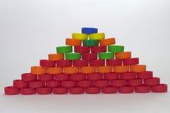 Vlakke die piramide uit gekleurde plastic kroonkurken op grijs wordt gemaakt royalty-vrije stock afbeeldingen