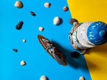 Vlakke mening van stuk speelgoed zeilboot en vuurtoren op blauwe en gele achtergrond met overzeese stenen en zeeschelpen royalty-vrije stock fotografie