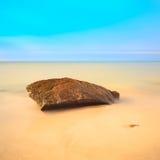 Vlakke rots op een gouden strand. Lange blootstelling. Stock Afbeeldingen