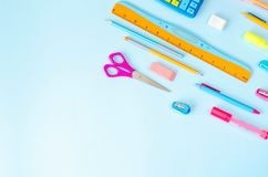 Vlakte van een verscheidenheid van kantoorbehoeften op een blauwe achtergrond stock afbeeldingen