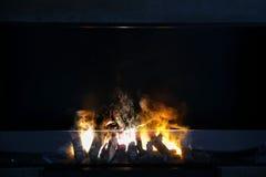 Vlam van brandhout het branden in moderne open haard stock afbeeldingen