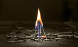 Vlam van de brandende gelijken in de duisternis amid puin op een hardhoutvloer Royalty-vrije Stock Foto