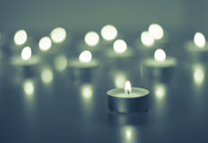 Vlam van vele kaarsen die op de blauwe kleur branden als achtergrond Stock Afbeeldingen