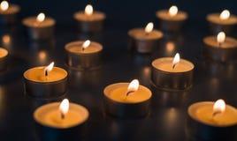 Vlam van vele kaarsen die op de bruine kleur branden als achtergrond Royalty-vrije Stock Afbeelding