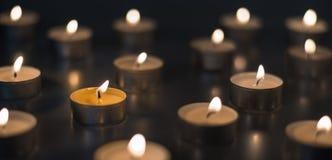 Vlam van vele kaarsen die op de bruine kleur branden als achtergrond Royalty-vrije Stock Fotografie