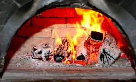 Vlammend hout in oude baksteenopen haard Royalty-vrije Stock Foto