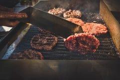 Vlammende grill en rundvleesburgers Royalty-vrije Stock Foto's