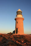 Vleeming Head Lighthouse. Lighthouse against a dawn sky with native grasses in the foreground. Sandstone of the lighthouse glows red from the rising sun Royalty Free Stock Photo