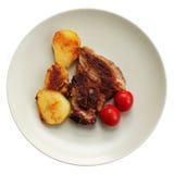 Vlees, aardappel en tomaat bij de plaat Royalty-vrije Stock Foto