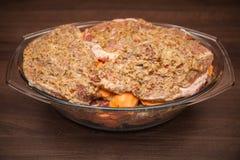 vlees dat in kruiden klaar voor baksel in de oven of op de grill met gehechtheid wordt gemarineerd gediend op een partij met vrie royalty-vrije stock fotografie