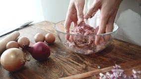 Vlees die voor koteletten of vleesballetjes in een roestvrij staal vullen De kokmengelingen hakken met de hand fijn Het concept:  stock videobeelden