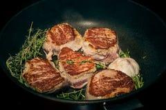 Vlees in een pan wordt gebraden die Vlees in een pan met kruiden wordt gebraden dat stock fotografie