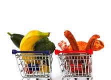 Vlees en groenten in twee boodschappenwagentjes, die op wit worden geïsoleerd Stock Fotografie