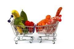 Vlees en groenten in twee die boodschappenwagentjes, op wit worden geïsoleerd Royalty-vrije Stock Foto's