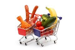 Vlees en groenten in twee die boodschappenwagentjes, op wit worden geïsoleerd Royalty-vrije Stock Afbeeldingen