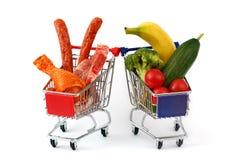 Vlees en groenten in twee die boodschappenwagentjes, op wit worden geïsoleerd Stock Afbeelding