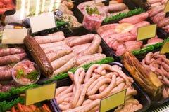 Vlees en worsten in een slagerij Stock Afbeeldingen